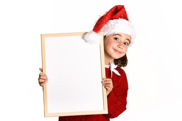 Маленькая девочка, улыбаясь с шляпу санта, холдинг белая доска