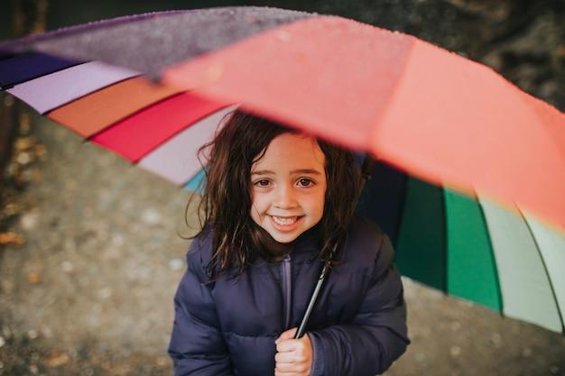 야외에서 가족 여행을 하는 동안 우산을 쓰고 웃고 있는 어린 소녀 초상화
