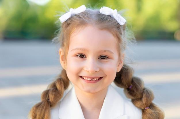 Маленькая девочка улыбается без переднего молочного зуба, растет постоянный коренной зуб. концепция гигиены полости рта. портрет милой смешной умной школьницы. обратно в школу. ребенок идет в первый класс.