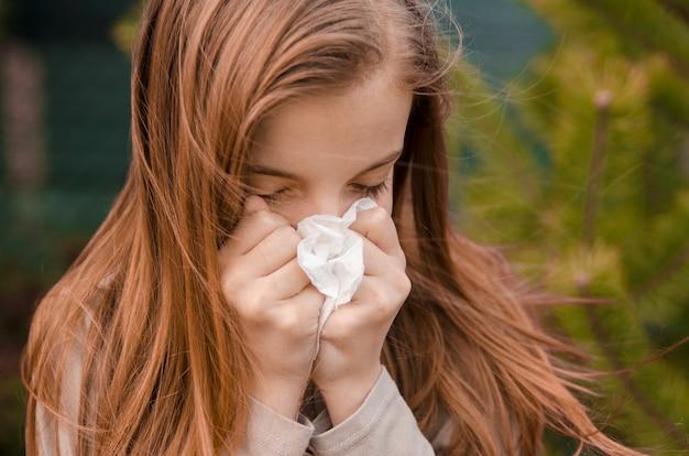 Маленькая девочка чихает в ткани под открытым небом в ветреный день