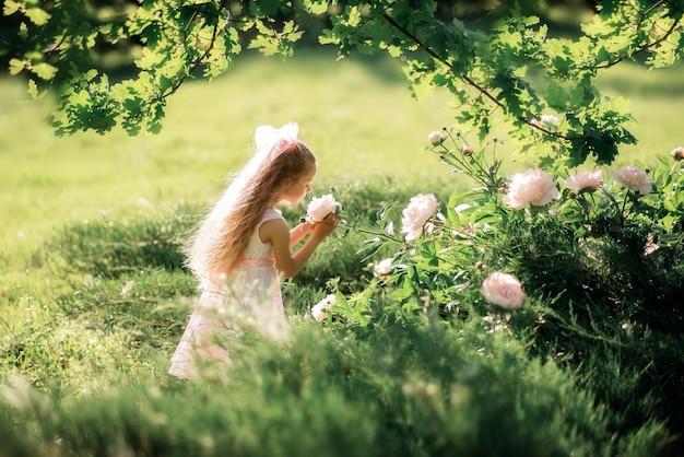 少女は花を嗅ぎます。夏は子供が牡丹の世話をします