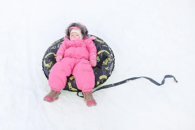 Little girl in  snow tube
