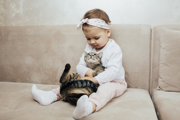 Little girl snuggling cute pet animal sitting on couch