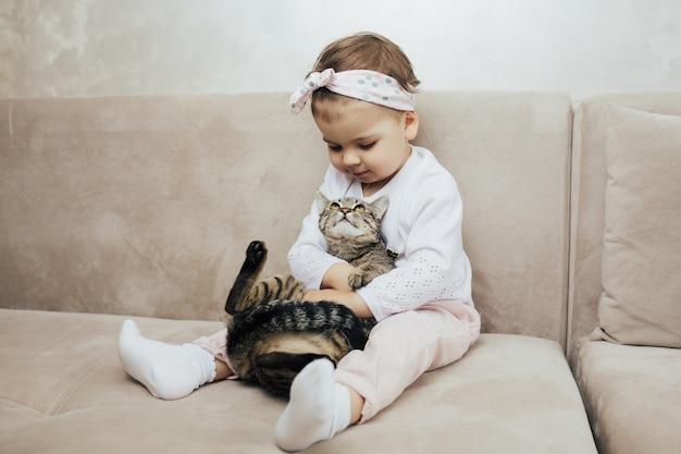 Маленькая девочка, прижимаясь к милому домашнему животному, сидящему на диване