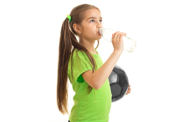 Little girl soccer player drinks water from a bottle isolated on white background