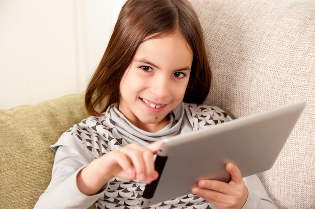 Little girl on sofa with touch tablet computer