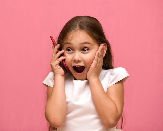 小さな女の子が電話で話します。驚き