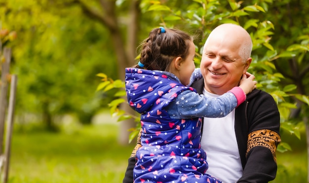 Little girl spending time with grandfather in the park