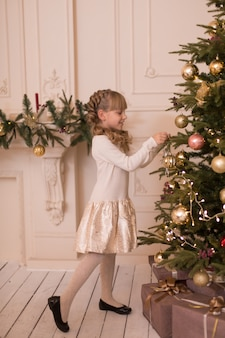 Little girl spends time decorating the christmas tree. preparing for the holidays. santa will be glad.