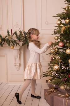 Маленькая девочка тратит время на украшение елки. готовимся к праздникам. санта будет рад.
