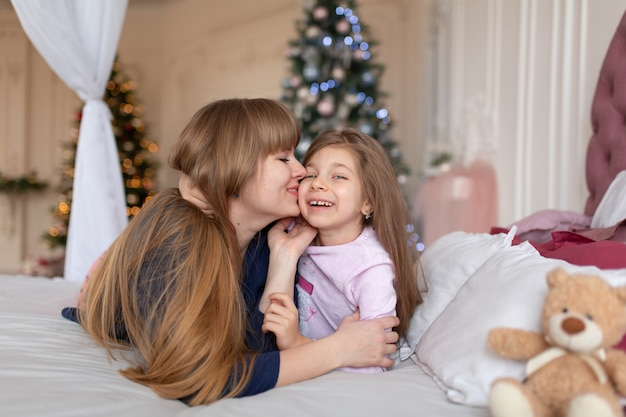 Little girl spends time playing with mom while lying in bed
