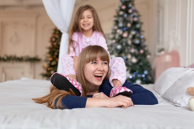 Маленькая девочка проводит время, играя с мамой, лежа в постели. рождественская сказка. счастливое детство.