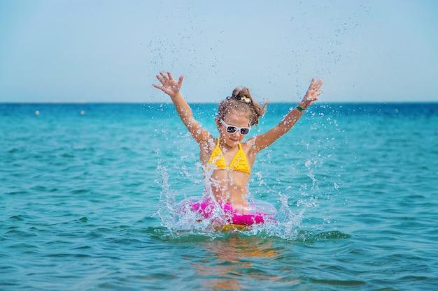 小さな女の子が海に水をはねかける