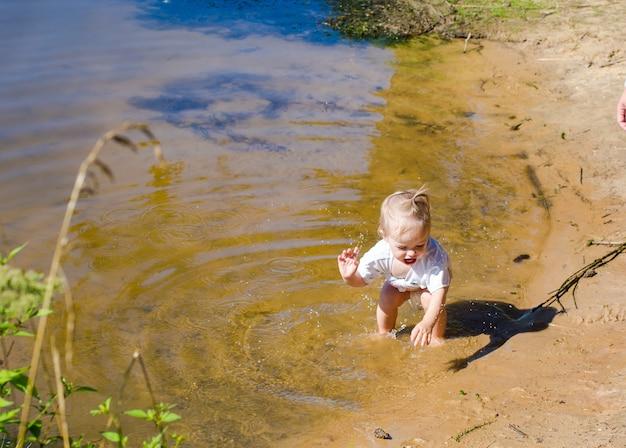 해안 근처 물에서 튀는 어린 소녀