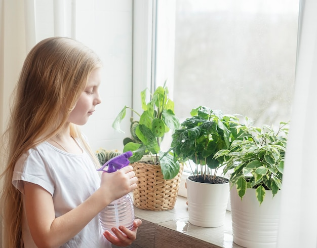 집 식물에 물이 튀는 어린 소녀. 가정 정원 가꾸기