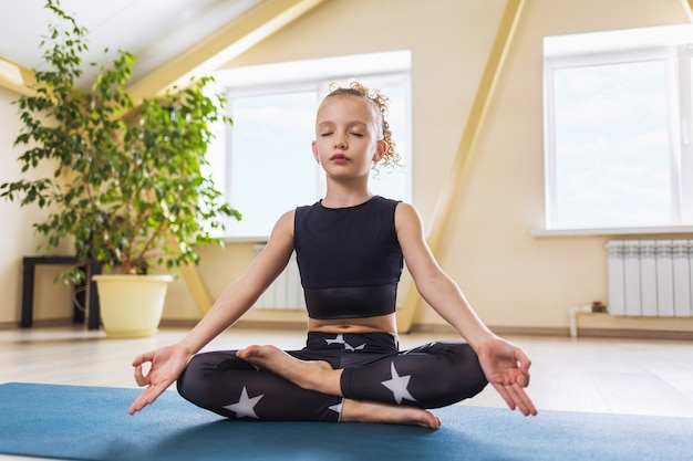 A little girl in sportswear practicing yoga is engaged in meditation sitting in the lotus position in the room
