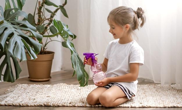 Маленькая девочка опрыскивает листья комнатных растений, ухаживает за растением монстера.