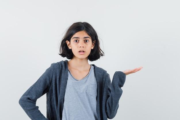 小さな女の子がtシャツ、ジャケットで手のひらを横に広げて困惑しているように見える、正面図。