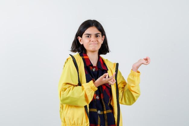 チェックのシャツ、ジャケットで手のひらを広げ、自信を持って見える少女