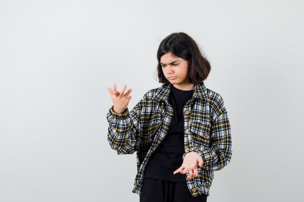 어린 소녀는 티셔츠, 재킷, 그리고 주저하는 듯한 표정으로 무의식적인 몸짓으로 손바닥을 펼칩니다. 전면보기.