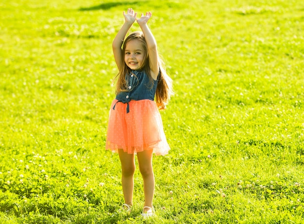 Little girl on spring field walk. child outdoor hands up. summer outside activity.