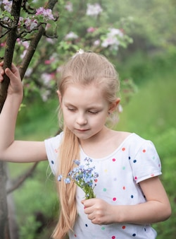 Little girl in a spring garden with blue forget-me-not flowers  in her hands