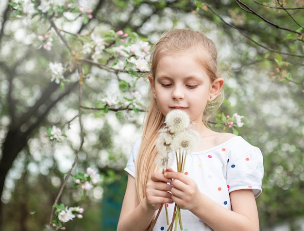 Little girl in a spring garden with white dandelions in her hands