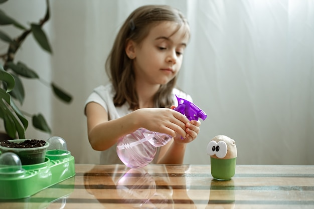A little girl sprinkles water on the toy head, with which the grass grows.