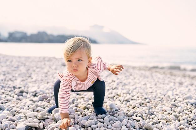 小さな女の子がしゃがんで小石のビーチで小石を求めて手を伸ばした