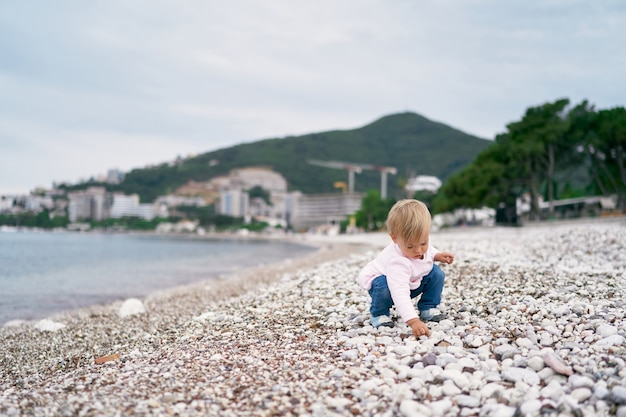 Little girl squatting on a pebble beach and holding a pebble in her hand
