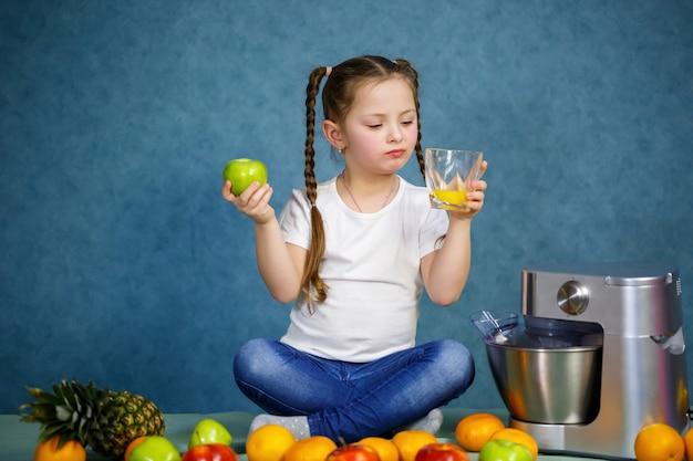 어린 소녀는 사과와 오렌지의 과일에서 신선한 주스를 짜냈습니다. 어린이를 위한 비타민과 건강한 영양.