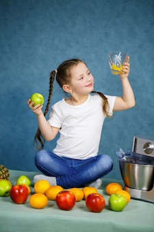 少女はリンゴとオレンジの果実からフレッシュジュースを絞りました。子供のためのビタミンと健康的な栄養。