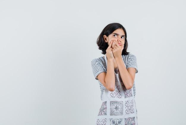 T- 셔츠에 뺨에 그녀의 여드름을 압박하는 어린 소녀