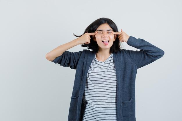 Bambina che strizza gli occhi, sporge la lingua in t-shirt