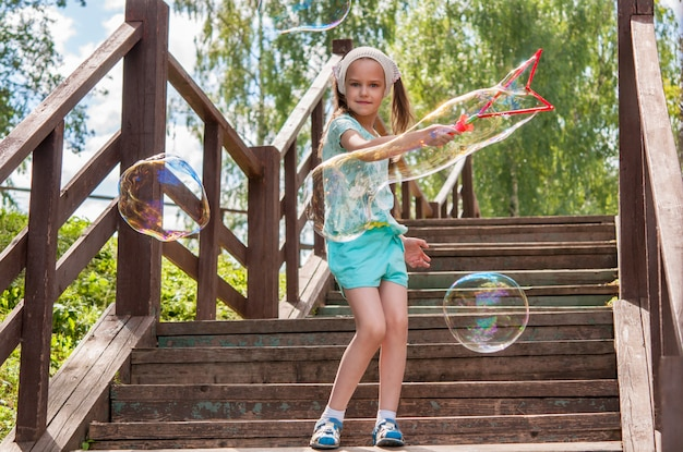 A little girl on the stairs lets out a huge soap bubble
