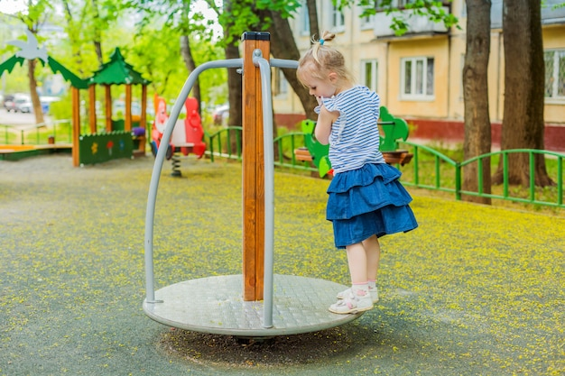 Little girl standing by spinning swing in playground