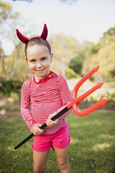 Little girl standing and dressing up as devil