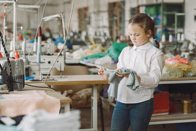 Little girl standing in the factory with a thread