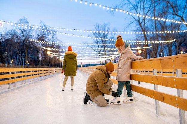 Little girl standing on figure skates while her father tying shoelace on her skate during their ride on ice rink