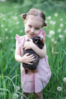 Little girl standing on grass holding guinea pig