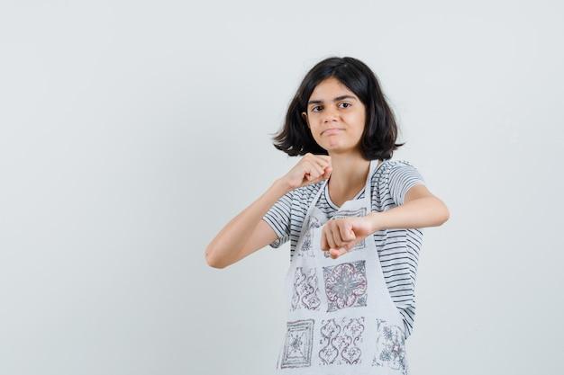 Tシャツ、エプロン、自信を持って戦闘ポーズで立っている少女