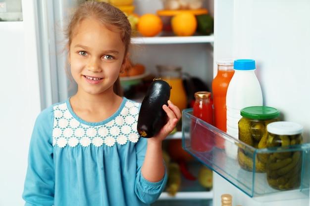 Маленькая девочка стоит перед холодильником и выбирает еду