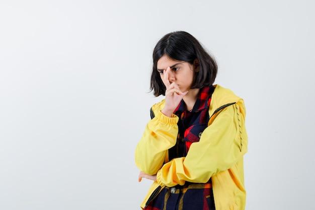Маленькая девочка стоит в позе мышления в клетчатой рубашке, куртке и смотрит вдумчиво, вид спереди.