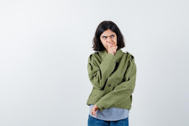 コート、tシャツ、ジーンズでポーズを考えて立っている少女は、思慮深く見えます。正面図。