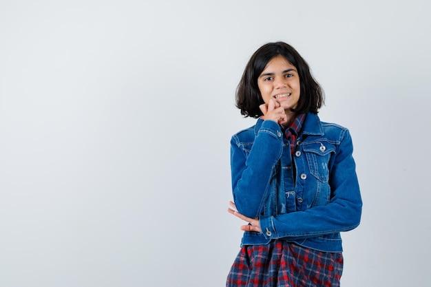 シャツ、ジャケット、陽気に見えるポーズを考えて立っている少女。正面図。