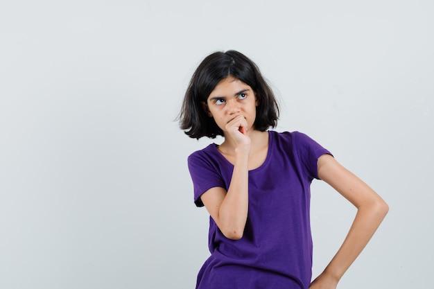 Tシャツを着てポーズを考えて立っている少女は躊躇している。