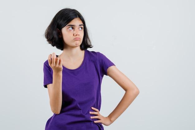 Tシャツでポーズを考えて立って困惑している少女