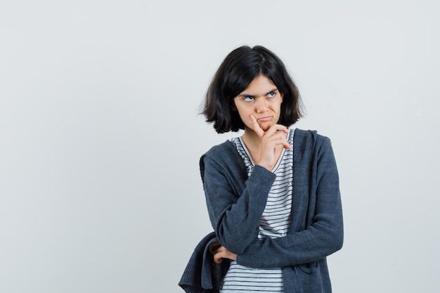 생각에 서있는 어린 소녀 티셔츠, 재킷 및 우울한 찾고 포즈