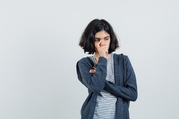 Tシャツ、ジャケット、疲れた顔でポーズを考えて立っている少女。