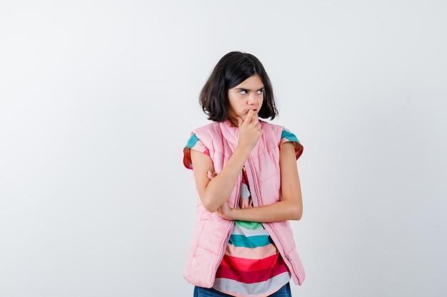 Tシャツ、フグベスト、ジーンズでポーズを考えて立っている少女は物思いにふける。正面図。
